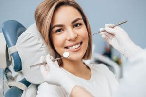 Woman smiling as dentist begins dental examination on gray background.